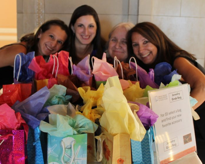 ATTENDEES GATHER behind gift bags at the 2016 Brain Injury Association of Rhode Island's secondannual Hidden Treasure Gala. This year's gala will take place on Nov. 3 at the Providence Biltmore. / COURTESY BRAIN INJURY ASSOCIATION OF RHODE ISLAND