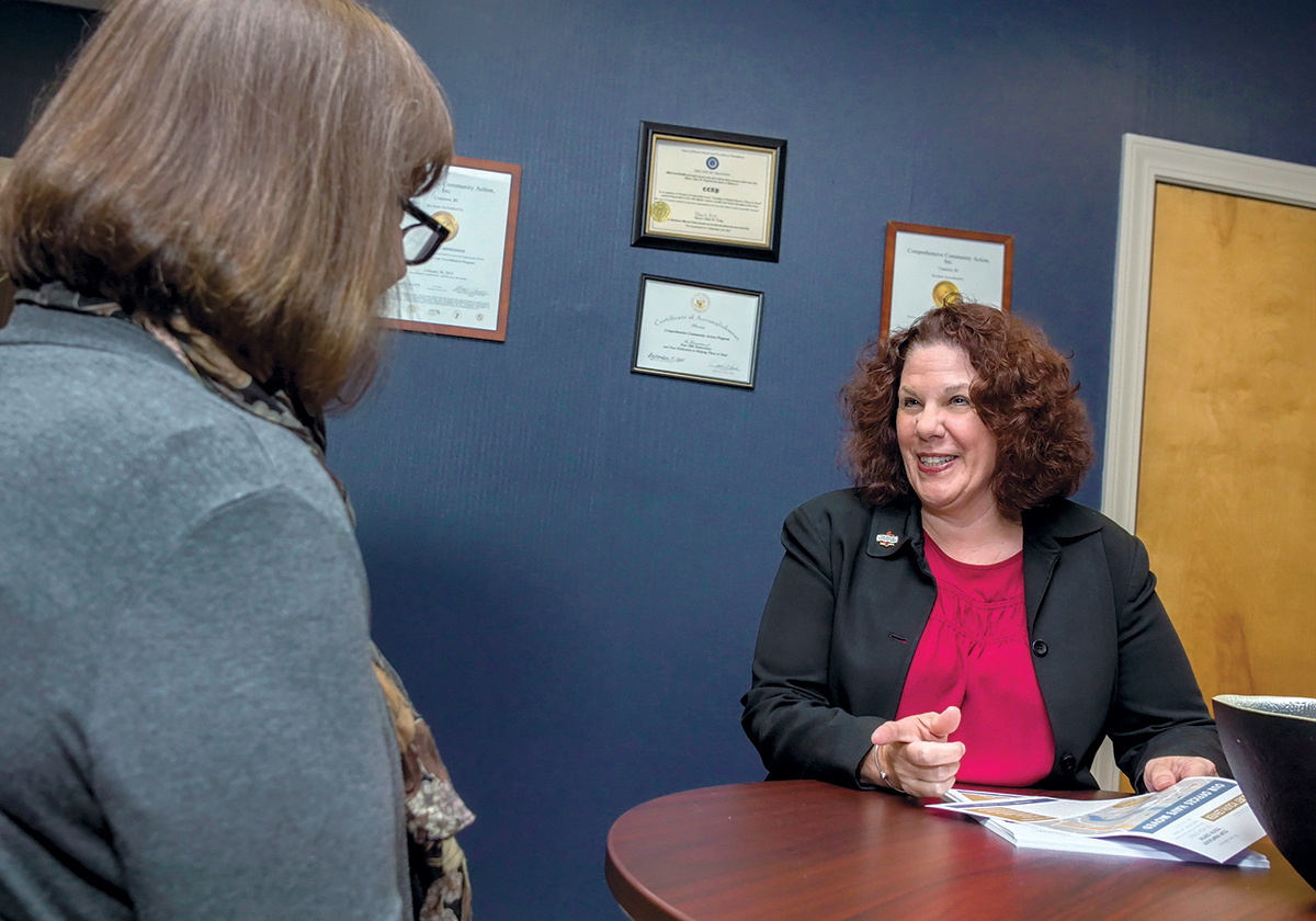 RICAA LEADER: Paula McFarland, right, executive director of the Rhode Island Community Action Association, speaks with administrative assistant Michelle Roy. McFarland received the United Way 211 Award for her work leading RICAA. / PBN PHOTO/MICHAEL SALERNO