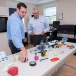 R&D TECHNOLOGIES will hold the grand opening of its additive manufacturing center in North Kingstown on Oct. 20. Above, from left, Justin and Andrew Coutu, president and CEO of the company, respectively, show off some of the objects produced in the company's 3-D printing-service bureau. / PBN FILE PHOTO/MICHAEL SALERNO