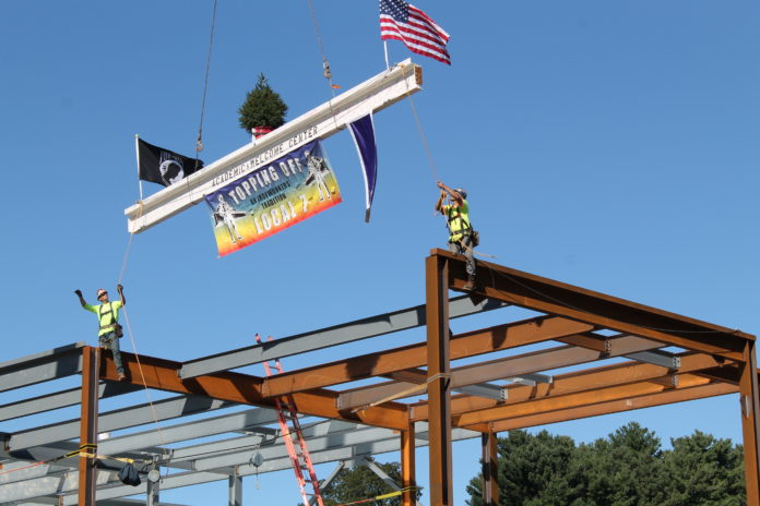 BOND CELEBRATES THE topping off, or the implementation of the final steel beam for a building project, of the new academic and welcome center at Stonehill College in Easton, which is scheduled to be completed in August 2018. / COURTESY BOND