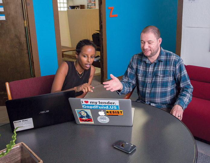 MOBILE HOTSPOTS: Muna Idriss, director of systems at Capital Good Fund, talks with CEO Andy Posner. For the past seven years, the nonprofit has purchased internet hotspots for traveling employees from Mobile Beacon.  / PBN PHOTO/TRACY JENKINS
