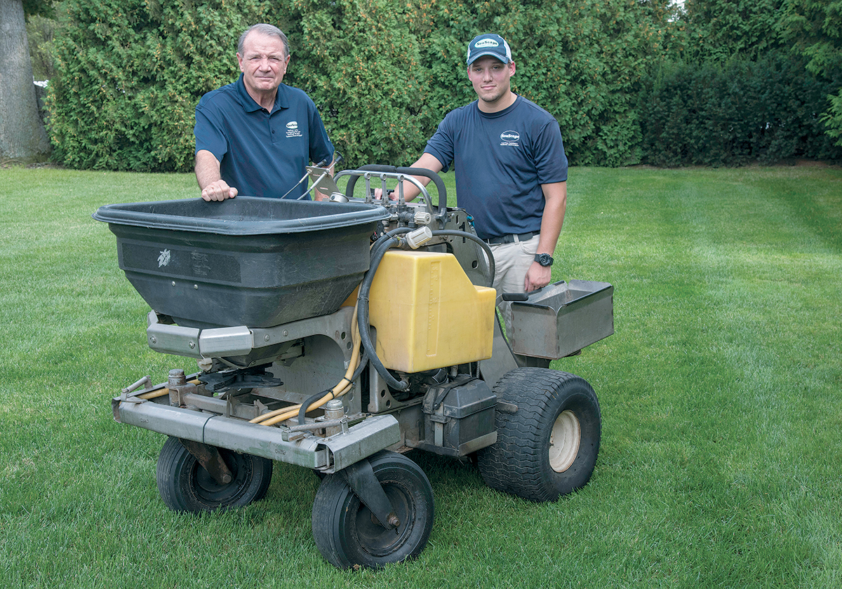 FIRST APPRENTICESHIP: Coventry-based SeaScape Lawn Care Inc. was chosen by the R.I. Nursery and Landscaping ­Association to host the industry's first apprenticeship program. From left, James Wilkinson, president, and Michael ­Graeminger, senior lawn technician, with their motorized fertilizer spreader. / PBN PHOTO/MICHAEL SALERNO