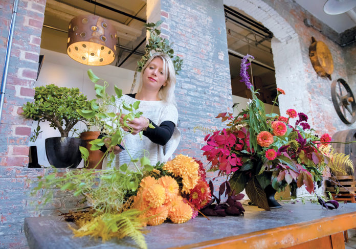 LOCALLY GROWN: Semia Dunne, owner of Flowers by Semia in Providence, constructs a centerpiece arrangement from 100 percent locally grown flowers. / PBN PHOTO/MICHAEL SALERNO