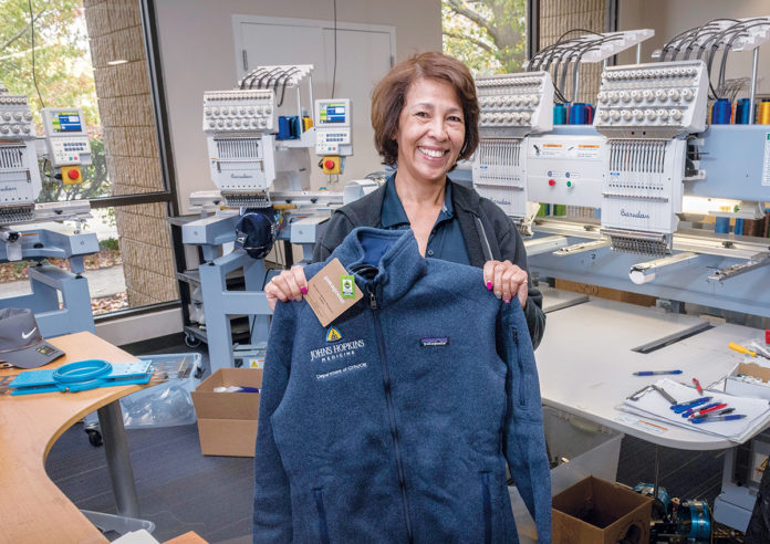 CO-BRANDED: ParsonsKellog in East Providence has a thriving partnership with Patagonia, featuring outdoor gear and apparel that is co-branded with various companies and the Patagonia label. Olga Montes, embroidery specialist, holds a vest branded for Johns Hopkins Medicine.  / PBN PHOTOS/MICHAEL SALERNO