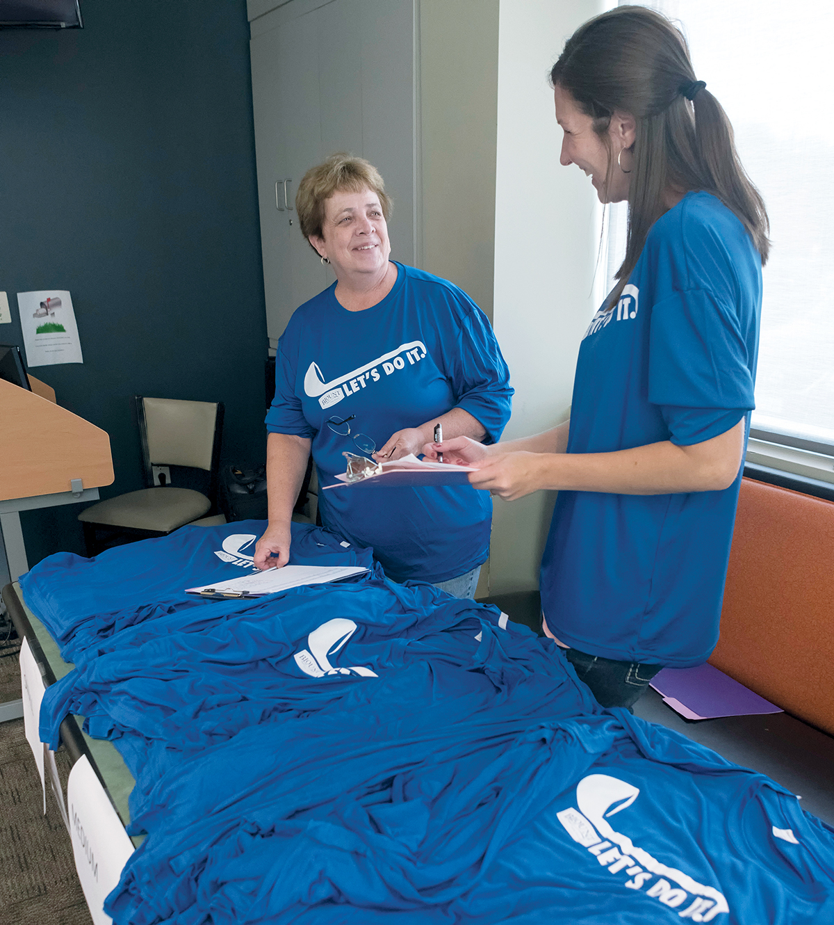RECOGNIZING STAFF: Shelly Swallow, payroll specialist, left, and Valerie Ball, senior HR manager, hand out T-shirts to employees at Blount Fine Foods as part of its corporate recognition program. / PBN PHOTO/MICHAEL SALERNO