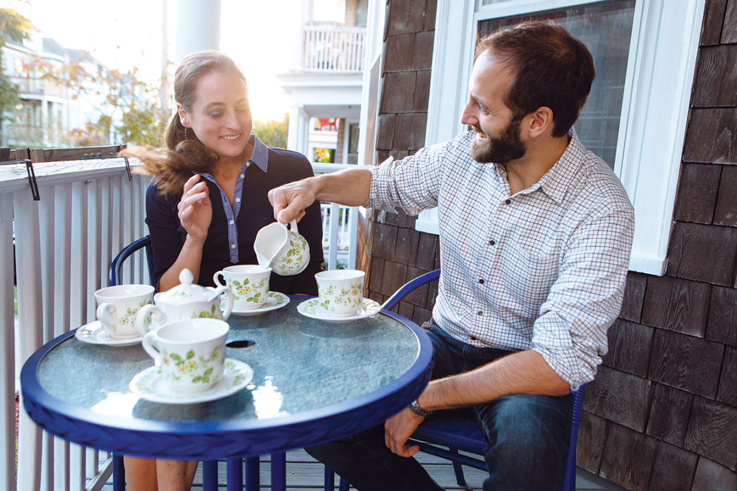 BARE NECESSITIES: Jessica Kowal drinks tea with her fiancé, Aaron, at their East Side apartment in Providence. The couple had to get rid of some possessions they didn't have room for.  / PBN PHOTO/RUPERT WHITELEY