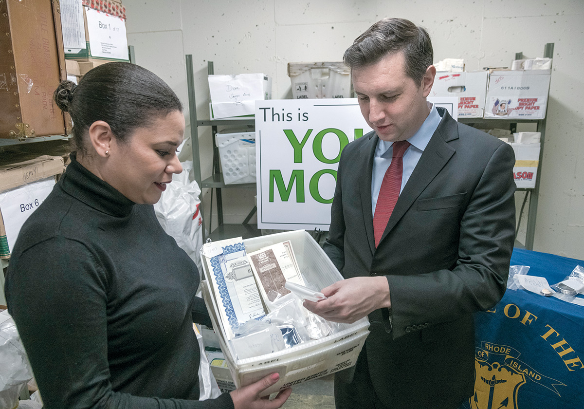 IN THE VAULT: Treasurer Seth Magaziner, with Lammis Vargas, director of the Unclaimed Property Division of Rhode Island, inside a vault with various items that ended up being unclaimed from bank safe-deposit boxes. / PBN PHOTO/MICHAEL SALERNO