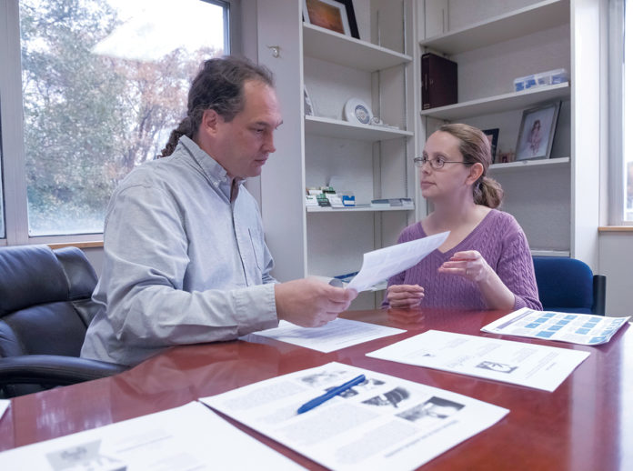 PAIN CLINIC: William and Jessica Cotton of B&B Medical Marijuana Evaluation Center in Warwick go over informational materials on marijuana. / PBN PHOTO/MICHAEL SALERNO