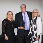 PROVIDENCE WARWICK CONVENTION and Visitors Bureau President and CEO Martha Sheridan (left) and Board Chair Dale Venturini (right) congratulate Hall of Fame Inductee Jeff Hirsh (center) at the PWCVB's Annual Meeting./ PHOTO COURTESY PWCVB