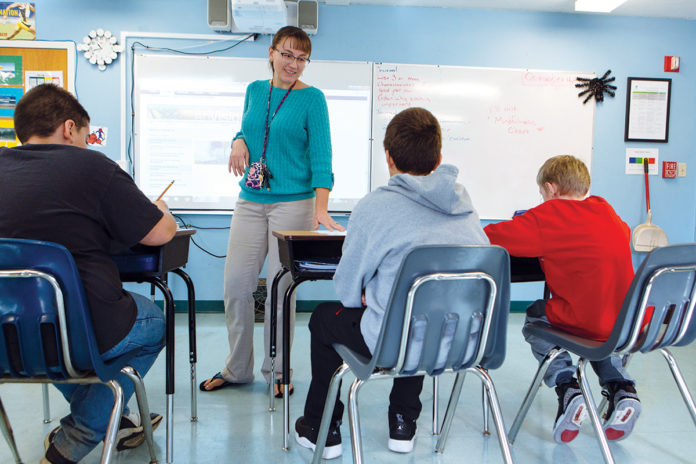 QUALITY TIME: Jana Gasbarro, middle school teacher, works with students in a special education class at St. Mary's Home for Children.   / PBN PHOTO/RUPERT WHITELY