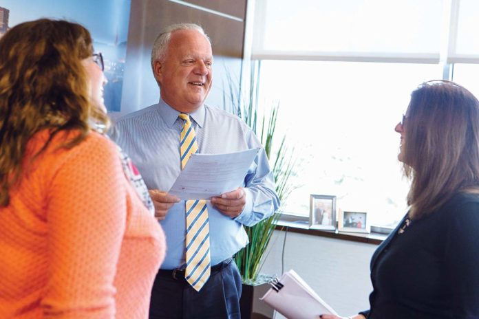 "PROSPEROUS HISTORY: William A. ""Bill"" White, Coastway president and CEO, speaks with Katie MacDonald, left, marketing manager, and Jeanette Fitz, chief financial officer, at the bank's Providence office.  / PBN PHOTO/RUPERT WHITELY"