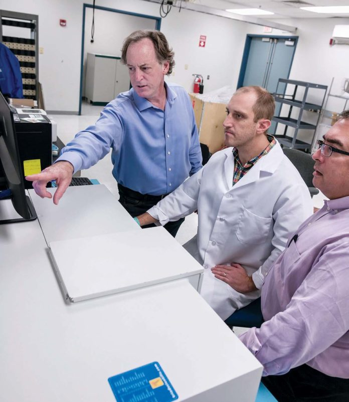 GUIDING RIGHT: From left, John D. Jarrell, founder of BioSci Labs in Coventry; Michael Stone, lab director; Jim Wilkinson, partner at Marcum, corporate sponsor of BioSci, calibrate a new piece of equipment for the lab. / PBN PHOTO/MICHAEL SALERNO