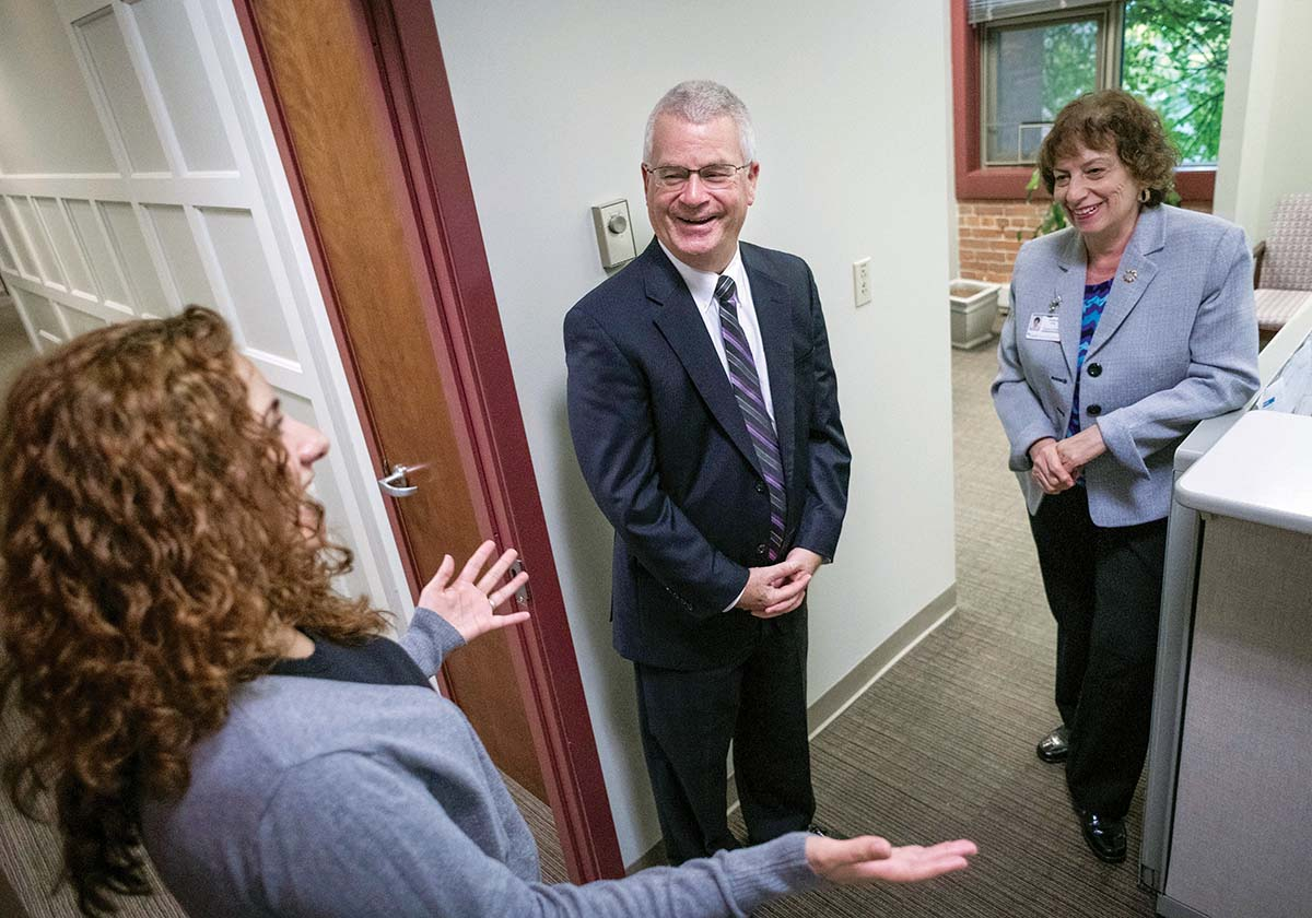 DYNAMIC DEDICATION: Dennis D. Keefe, retiring president and CEO of Care New England, speaks with Malinda Caetano, executive assistant, left, and Frances Giatas, executive assistant to Keefe, at their Providence office. / PBN PHOTO/MICHAEL SALERNO