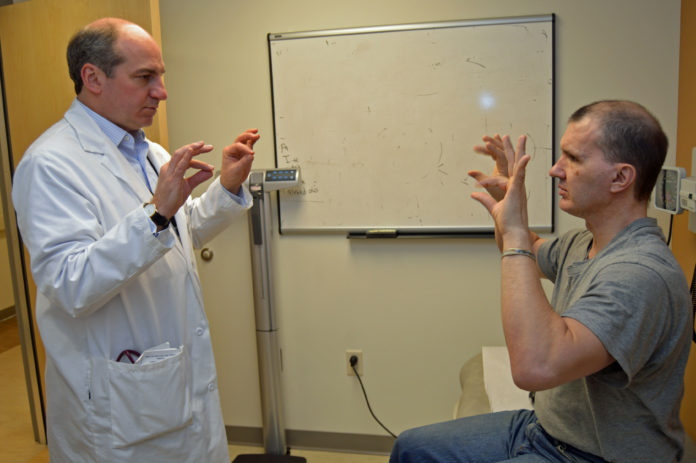 DR. W. CURT LAFRANCE, co-principal investigator for a new study that hopes to shed light on the mechanism behind seizures associated with post-traumatic epilepsy and psychogenic nonepileptic seizures, conducts a finger-tapping exercise with Army and Navy Veteran Ernest J. Avery of West Warwick as part of an exam at the Providence VA Medical Center. Seizures are a common result of traumatic brain injury, especially in Veterans. / COURTESY OCEAN STATE RESEARCH INSTITUTE