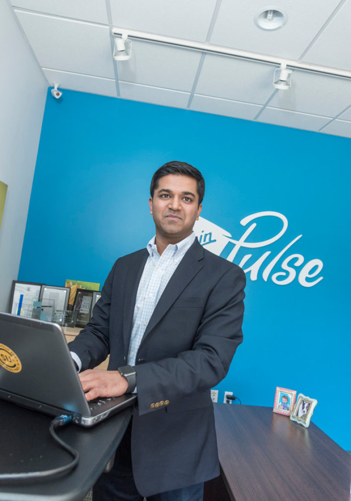 PICKING PROVIDENCE: Dr. Rajiv Kumar, president and chief medical officer of Virgin Pulse Institute, in the company's former space in Providence. Virgin Pulse announced the relocation of its global headquarters to Providence from Framingham, Mass., on Monday. / PBN FILE PHOTO/MICHAEL SALERNO