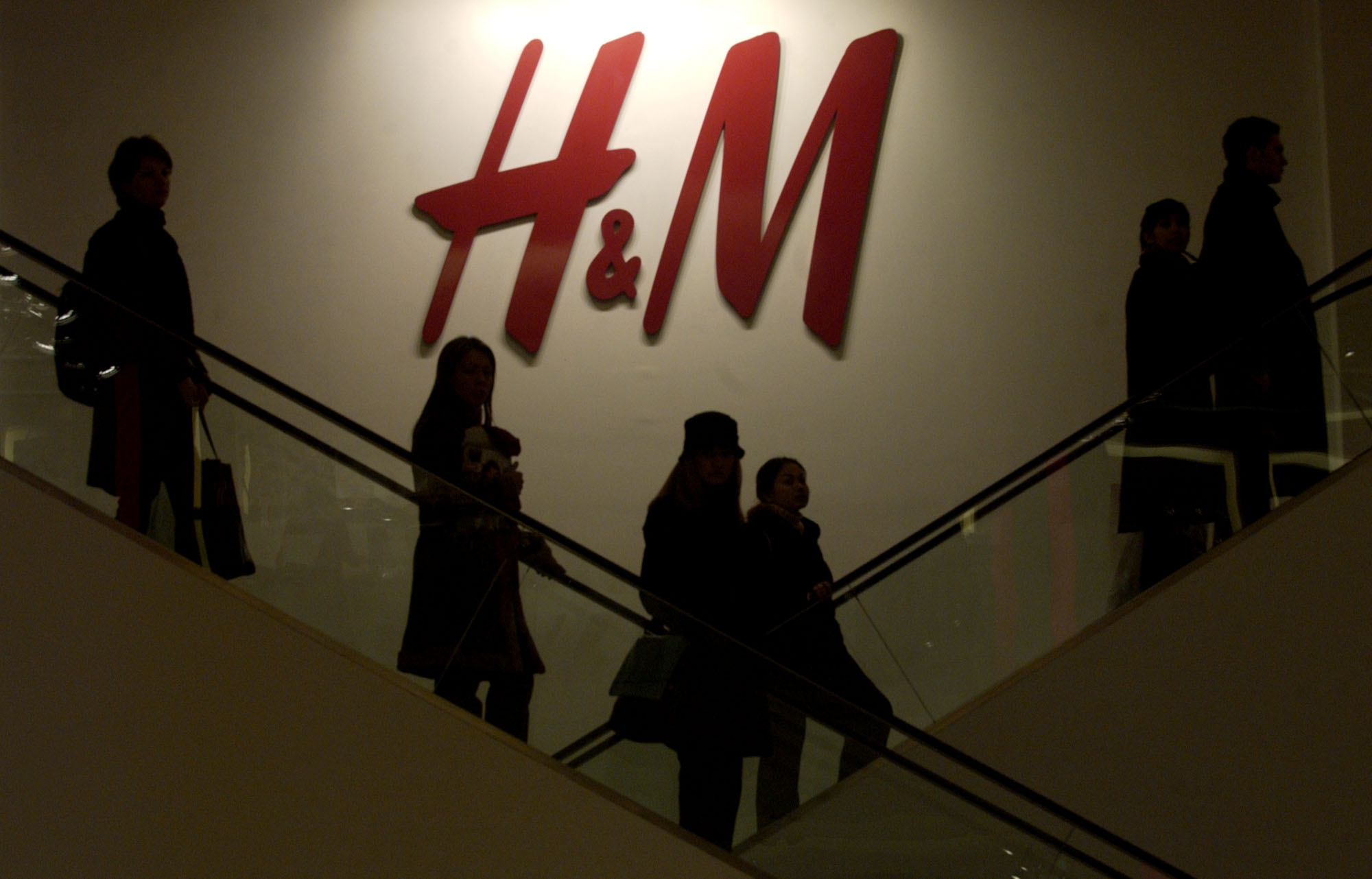 CUSTOMERS RIDE ESCALATORS in an H&M store in New York. / BLOOMBERG FILE PHOTO/DANIEL ACKER