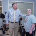 THOMAS P. KANE, left, president and CEO of AccessPoint RI, assists Christopher Perry of Coventry with his workout. / PBN FILE PHOTO/MICHAEL SALERNO