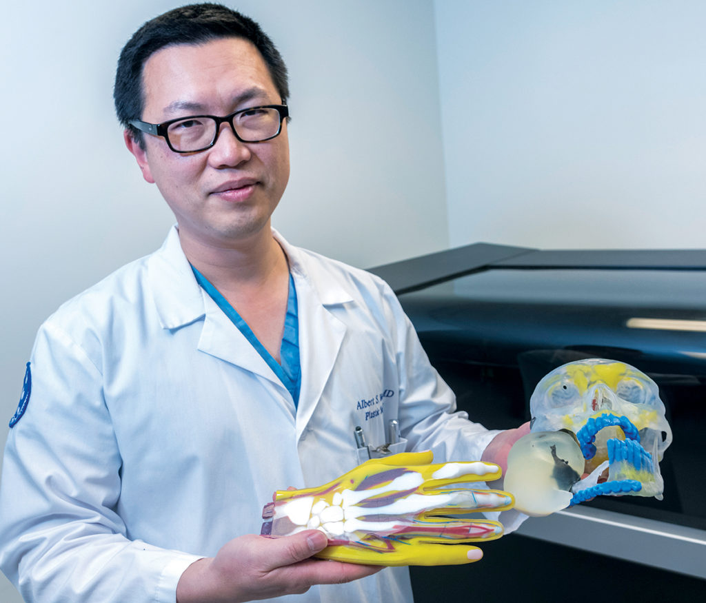 MEDICAL MODELS: Dr. Albert Woo, chief of pediatric plastic surgery and director of the Cleft and Craniofacial Center at Hasbro Children's Hospital, shows off various surgical medical models printed with the hospital's 3-D printer. / PBN PHOTO/MICHAEL SALERNO