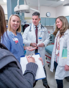 TREATMENT TEAM: Dr. Peter Graves, chief of emergency medicine at Kent Hospital, with the opioid-overdose treatment team. From left, Coleen Carlon, licensed mental health clinician; Alyssa Quinn, registered nurse; Graves; and Alicia Zuwallack, emergency room pharmacist, go over procedures for an emergency. Inset, the drug Naloxone, which is used to combat an opioid overdose. / PBN PHOTO/MICHAEL SALERNO