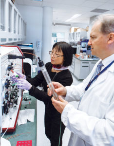 LUBRIS LAB: Dr. Ling Zhang, left, and Dr. Gregory D. Jay, owner of Lubris LLC, work on the AKTA machine, which purifies antibodies, at the Lubris lab. / PBN FILE PHOTO/RUPERT WHITELEY