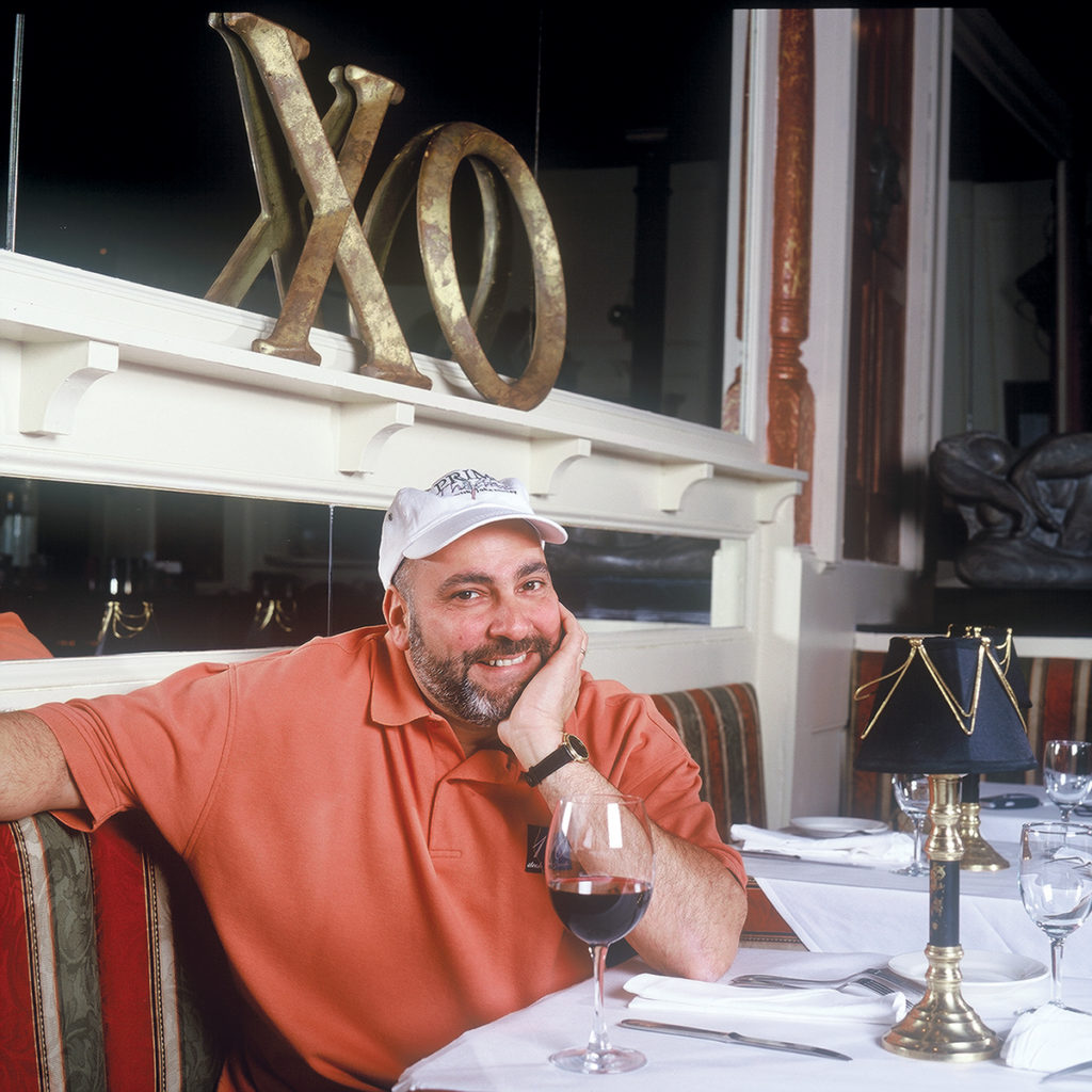 CELEBRATION: Chef John Elkhay, maestro of Chow Fun Food Group, at the table at his XO Café restaurant, which is offering menu prices from 1997 for a limited time in December in celebration of 20 years in Providence. / COURTESY CHOW FUN FOOD GROUP