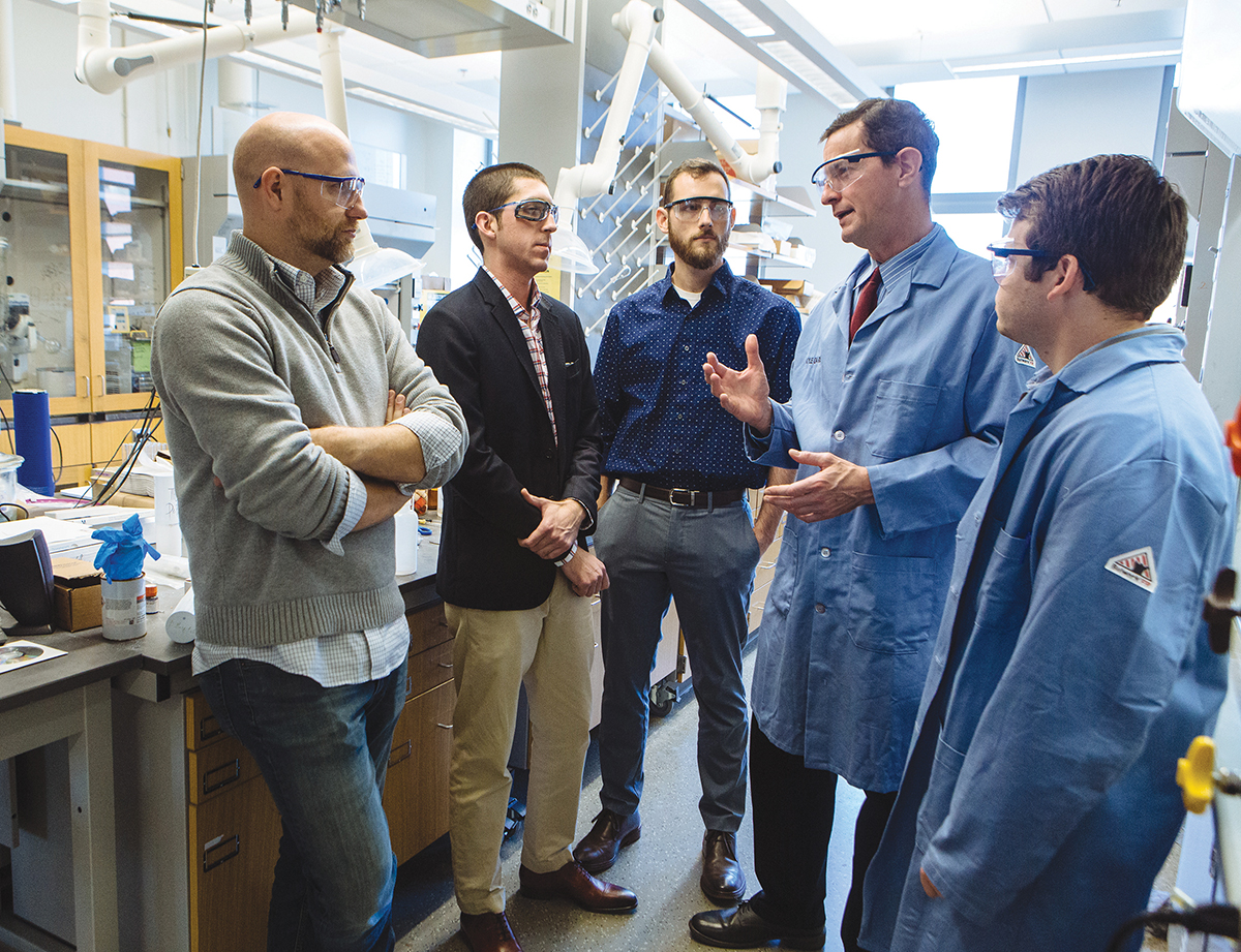 TEAM MEETING: From left, Brenton DeBoef, professor of chemistry at the University of Rhode Island, and Alcinous Pharmaceutical team members Nicholas DaSilva, CEO and Ph.D. student in the URI College of Pharmacy; Benjamin Barlock, chief technology officer and Ph.D. student in the URI College of Pharmacy; David Worthen, chief operations officer and URI assistant professor in the Department of Biomedical and Pharmaceutical Sciences and the Department of Chemical Engineering; and Ken Rose, chief scientific officer and Ph.D. student in the URI College of Pharmacy, discuss Alcinous' latest research project. / PBN PHOTO/RUPERT WHITELEY