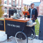 MOBILE COFFEE: Cole Criollos operates one of two of The Nitro Cart's mobile coffee carts in Providence's West Side neighborhood. The company was launched in 2016 by co-owners Audrey Finocchiaro and Sam Lancaster. / PBN PHOTO/RUPERT WHITELEY