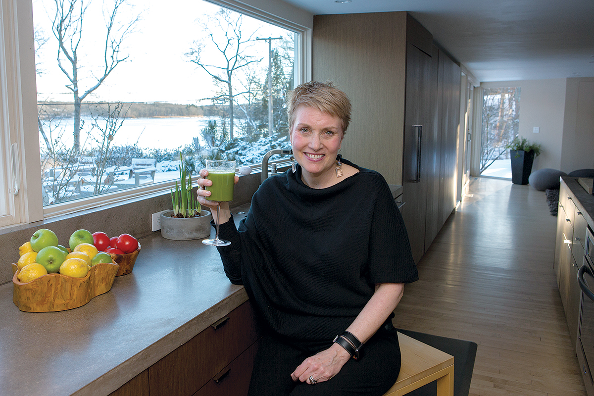 COLD CURE: Katie McDonald, corporate health coach and owner of bnourished, sits at her kitchen counter enjoying a green juice, a remedy/prevention for winter colds. / PBN PHOTO/KATE WHITNEY LUCEY