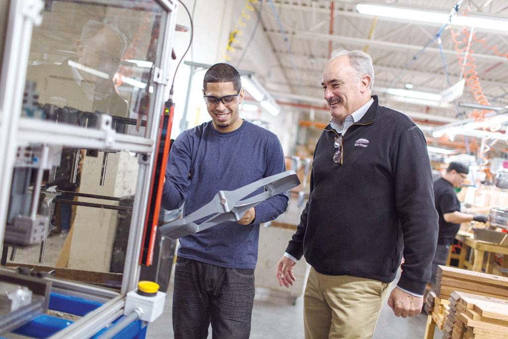 """BROADER FIELD: WaterRower Inc. President and CEO Peter King and assembly operator Alex Aponte at the company's new headquarters in Warren. King says WaterRower has turned to outside agencies to assist in its hiring process, """"to give us a broader field of capture."""" / PBN PHOTO/RUPERT WHITELEY"""
