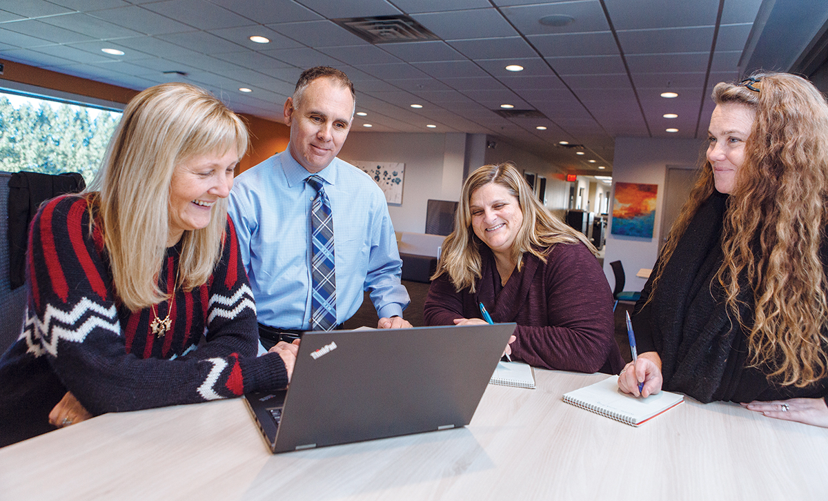 """COMMUNITY CONNECTION: Kurt Noyce, president of Embrace Home Loans Inc. in Middletown, said the company's relationship with local colleges and job-development organizations has provided Embrace with """"eager, energetic and ethical employees."""" Pictured, from left: Claudia Mobilia, senior vice president of loan operations; Noyce; Shawn Cary, bank finance manager; and Shannon Timek, closing team leader. / PBN FILE PHOTO/RUPERT WHITELEY"""