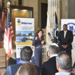 GOV. GINA M. RAIMONDO at the podium next to Director of Veterans Affairs Kasim Yarn at the launch of RIServes, a coordinated network of public, private and nonprofit organizations designed to help service members, veterans and their families find services they need in Rhode Island. / COURTESY R.I. OFFICE OF VETERANS AFFAIRS