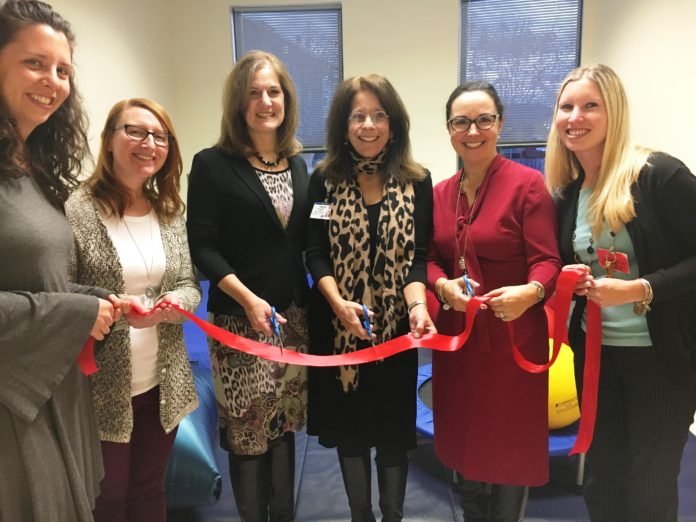 CUTTING THE RED RIBBON at the opening of the Youth Trauma Program's new SMART Room are, from left: Hallie Riggs and Megan Tavares of the Youth Trauma Program; Deidre Donaldson, chief clinical officer, The May Institute; Jennifer Salem-Russo, clinical coordinator, Youth Trauma Program; Julie Gagliardi, vice president of corporate giving and community relations, BayCoast Bank; and Stephanie Sayles, of the Youth Trauma Program. / COURTESY BAYCOAST BANK