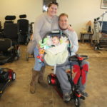 MICHAEL LEAVITT WITH his wife and daughter after winning a Pride Go-Go scooter during the Mobility Equipment Recyclers of New England's 2017 Gift of Mobility event. / COURTESY MOBILITY EQUIPMENT RECYCLERS OF NEW ENGLAND