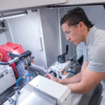 MEASURING UP: Otto Fernandez, a worker at Mahr Federal Inc. in Providence for the past 18 months, and a student in the Shipbuilding/Marine and Advanced Manufacturing Institute machinist program at New England Institute of Technology, takes measurements on a grinding machine. / PBN PHOTO/­MICHAEL SALERNO