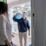 CONTAMINANT FREE: Paul Cicillini, carrier for Crystal Springs Water Co., delivers water to the apartment of Natalie Drozhzhin in Providence. Customers are willing to pay monthly for delivery of drinking water they know is free of contaminants. / PBN PHOTO/MICHAEL SALERNO