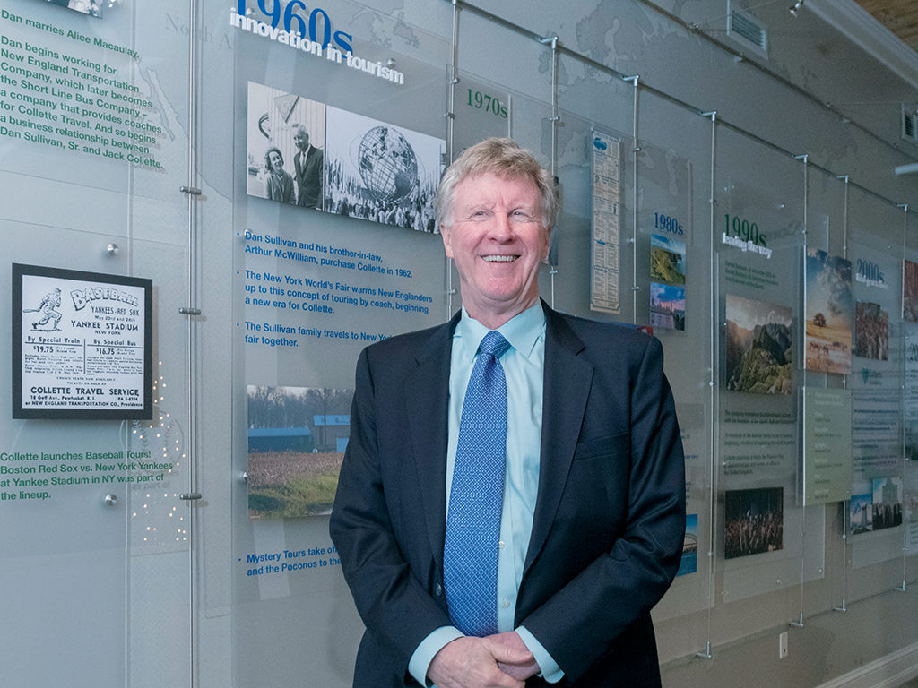 FAMILY OWNED: Collette CEO and President Dan Sullivan Jr. stands in front of the company's timeline at its Pawtucket headquarters. Sullivan succeeded his father, Dan Sullivan, as CEO in 1990. / PBN PHOTO/MICHAEL SALERNO