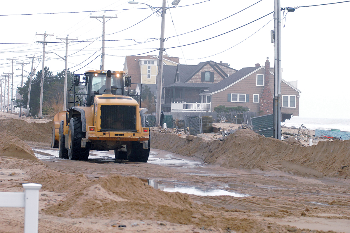 "DIGGING OUT: A truck clears sand off Atlantic Avenue in the Misquamicut community of Westerly following ""Superstorm"" Sandy in 2012. Today the town is still dredging 20,000 cubic yards of sand from Winnapaug Pond deposited there during the storm.  / PBN FILE PHOTO/BRIAN MCDONALD"