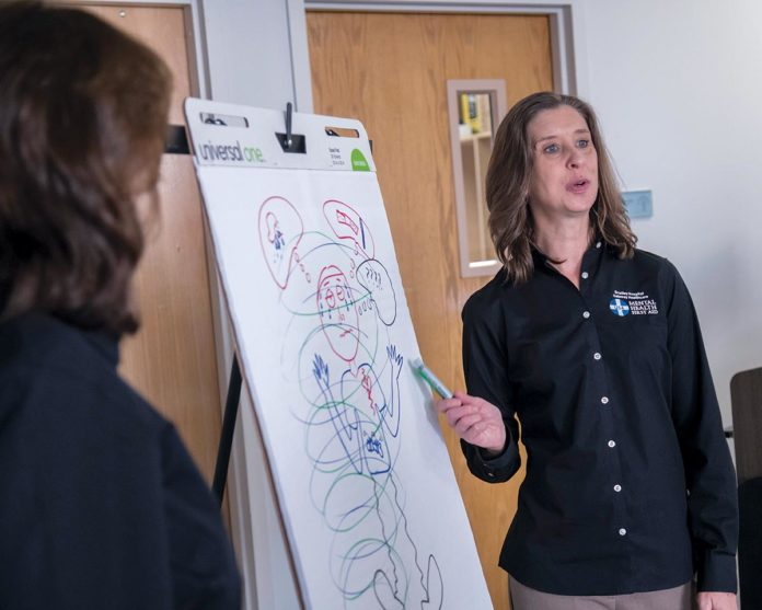 PUBLIC TRAINING: A group of Mental Health First Aid trainers for Lifespan Corp. discusses strategies for helping the public identify, understand and respond to signs of mental illness. From left, Katherine Desjarlais, milieu associate at Lifespan, and Kimberly LaFountain, behavioral education development specialist at Bradley Hospital. / PBN PHOTO/MICHAEL SALERNO