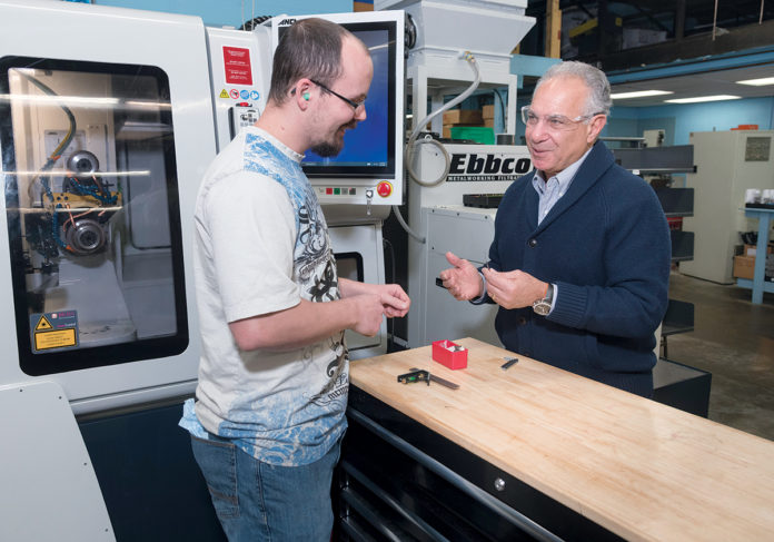 TALKING SHOP: John Lombari, right, sold his manufacturing company, R.I. Carbine Tool Co. based in Smithfield, earlier this year. Lombari speaks with Danny Loiselle, CNC machine programmer/operator. / PBN PHOTO/­MICHAEL SALERNO
