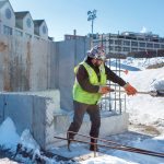 SNOW REMOVAL: A Shawmut Construction worker shovels snow from the work site at 225 Dyer St. in Providence. Construction crews must deal with the winter elements to meet project deadlines. / PBN PHOTO/RUPERT WHITELEY