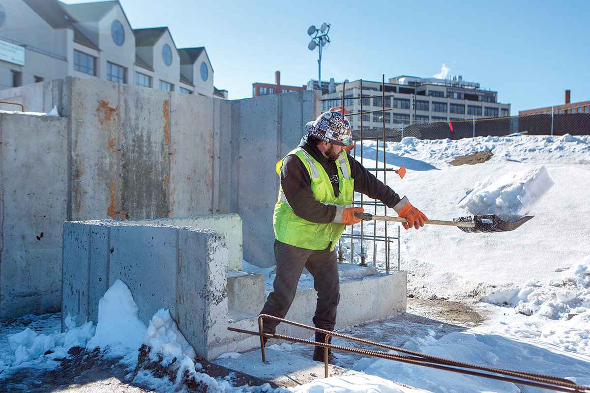 SNOW REMOVAL: A Shawmut Construction worker shovels snow from the work site at 225 Dyer St. in Providence. Construction crews must deal with the winter elements to meet project deadlines. / PBN PHOTO/­