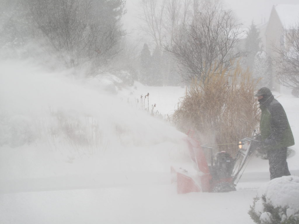 SNOW CONTINUES TO WALLOP Rhode Island with blizzard conditions. Above, a Warwick resident snowblowing his driveway mid-storm. / PBN PHOTO/JANE BLOTZER