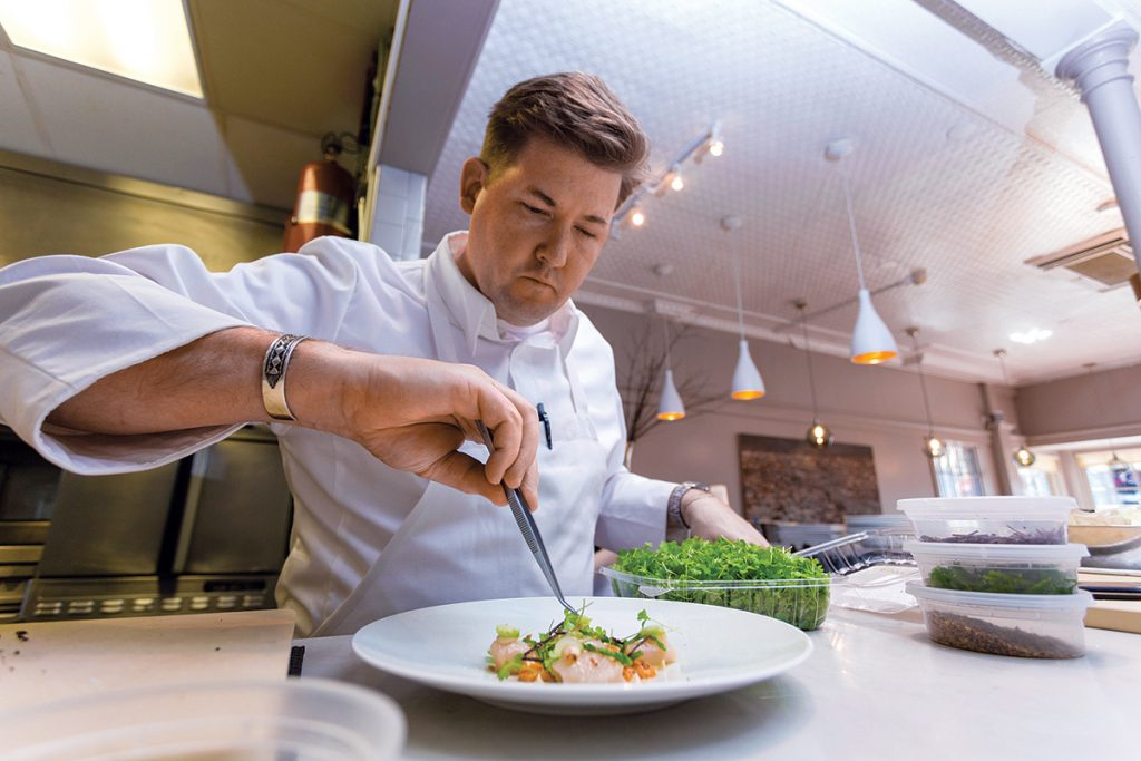 READY TO SERVE: Chef Champe Speidel, of Persimmon, puts the finishing touches on a dish during Providence Restaurant Weeks, held Jan. 14-27. / COURTESY NICHOLAS MILLARD/GOPROVIDENCE.COM