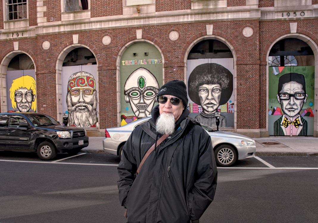 "CELBRATING ­DIVERSITY: Bert Crenca, a Providence artist and founder of AS220, stands in front of ""Types,"" a series of five murals he painted on the historical façade of the Providence National Bank building at 35 Weybosset St, which is meant to celebrate the diversity of people. / PBN PHOTO/