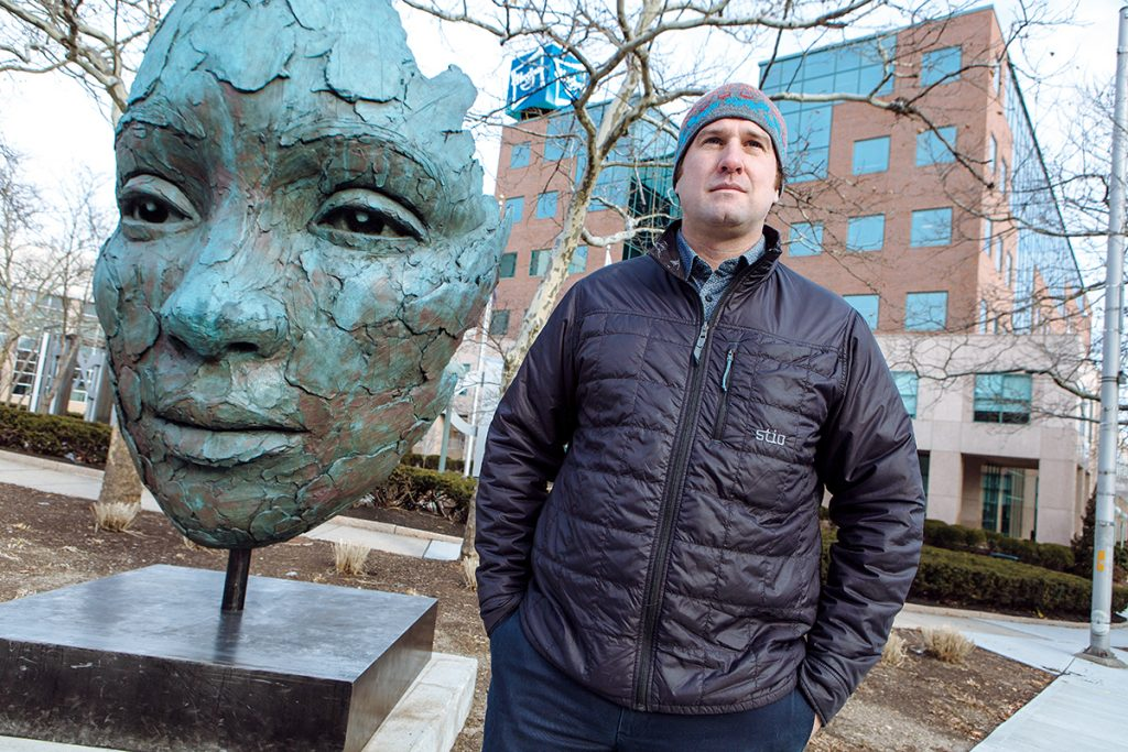 UP CLOSE: Yarrow Thorne, founding director of The Avenue Concept, stands next to Colossal Fragment, a sculpture by South African artist Lionel Smit. The piece was at the intersection of Fountain and Empire streets, near the Hasbro Inc. building, in Providence for six months but was moved to Miami in January. / PBN PHOTO/RUPERT WHITELEY