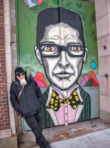 STANDING TALL: Providence artist and AS220 founder Bert Crenca leans in front of one of the five murals he painted on the historical façade of the Providence National Bank building at 35 Weybosset St. in Providence. / PBN PHOTO/MICHAEL SALERNO