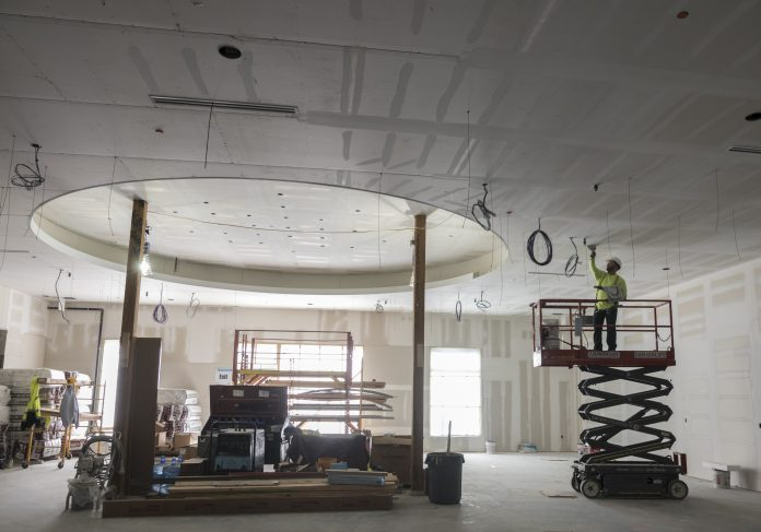 CONSTRUCTION OF THE HOTEL at Twin River Casino in Lincoln is near completion. Above, Cory Viera, dry wall finisher for H. Carr, works on one of the ceilings on the first floor. / PBN PHOTO/MICHAEL SALERNO