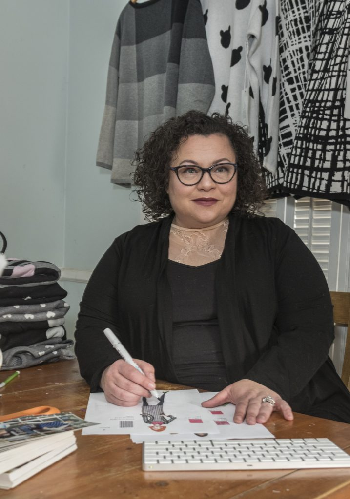 NEW ­DESIGNS: Elana Carello, owner of Elana Carello Sweaters, sketches new designs. She has found success in pop-up shops and artisan shows and has seen her sales grow. / PBN PHOTO/­MICHAEL SALERNO