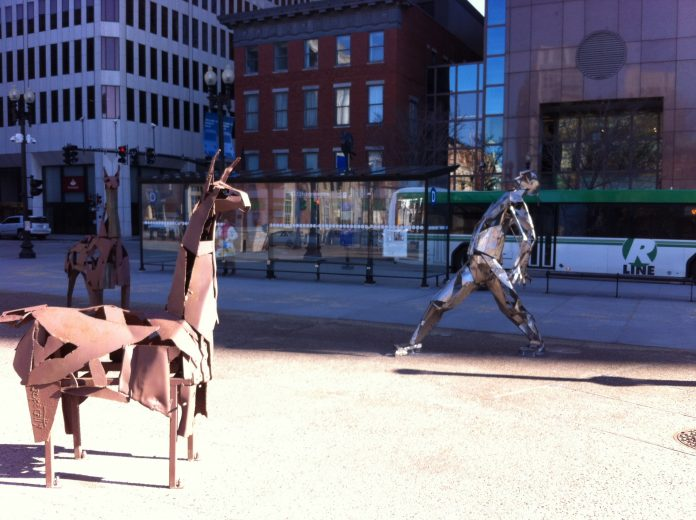 TWO 6-FOOT LLAMAS and a man made of car bumpers are among the scrap art sculptures installed in Kennedy Plaza in Providence. / PBN PHOTO/ MARY MACDONALD