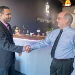 FIRST CLIENT: Evanisio Oliveira, left, owner of Universal Cleaning LLC, shakes hands with Thomas Lent, president and CEO of Thielsch Engineering, which owns Creative Environment Corp. Lent was Oliveira's first client when he started his cleaning business. / PBN PHOTO/MICHAEL SALERNO